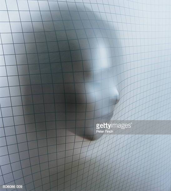 Young woman's face pushing through soft metallic grid