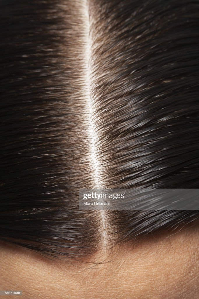 Young woman's hair parting, close-up : Stock Photo