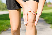 Young woman's hand touching her knee during running time on footpath. Joint pain. Sporty problem and solution. Close up. Front view.