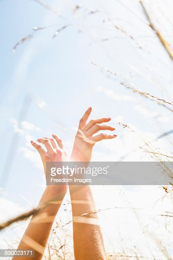 Young womans hands amongst long grass