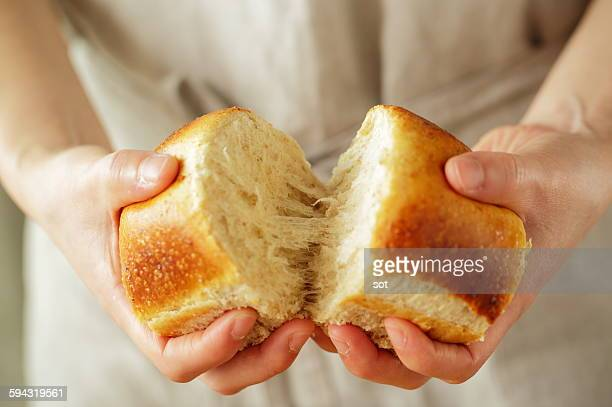 Young woman's hands breaking bread,close up