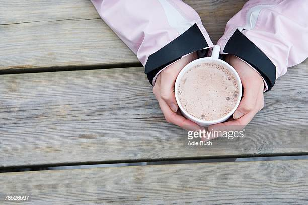 young woman's hands holding cup of hot chocolate, close-up, high angle view