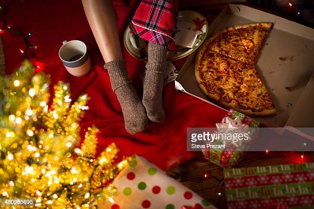 Young woman's legs amongst christmas gifts and pizza box