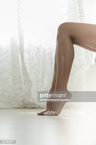 Young woman's legs in bedroom