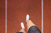 Young woman's legs in white shoes standing on stadium track in summer day. Daily outdoor active lifestyle. Enjoying sport. Training time. Point of view shot. Part of body.