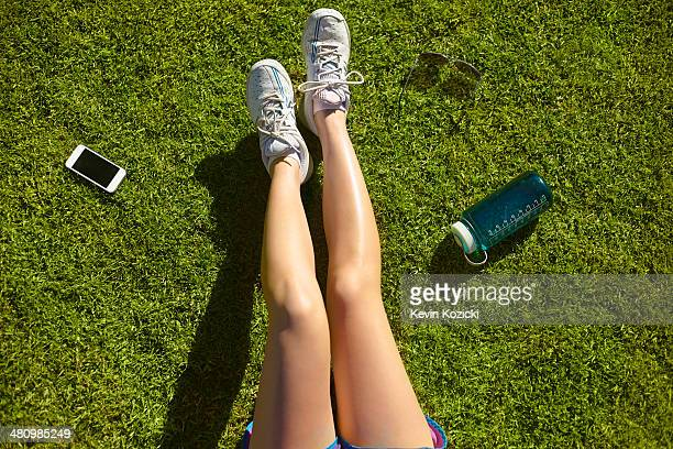Young woman's legs on sunlit grass in park