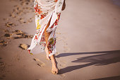 Close up of woman's legs in beach cover up taking a walk barefoot on the sand