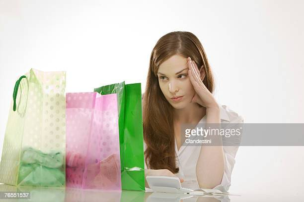 Young woman with shopping bags, head in hands
