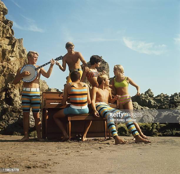 Junge Frauen und Männer, die Spaß am Strand
