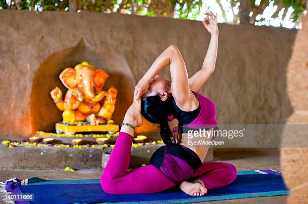 A young women and yoga teacher practices advanced yoga postures and asanas like raja kapotasana king pigeon pose in a traditional yoga shala at Yoga...