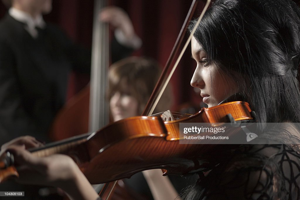Young women and young man playing string instruments