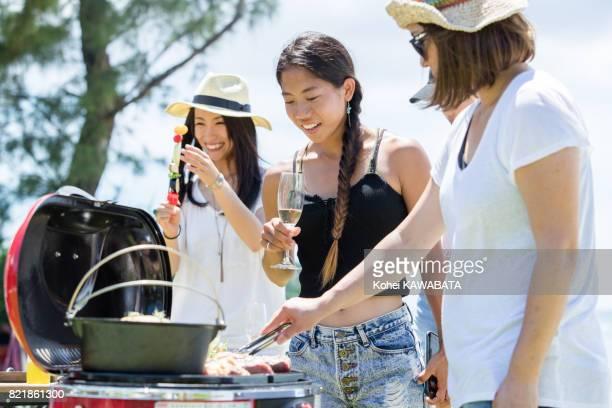 若い女性がバーベキューで楽しんでいます。