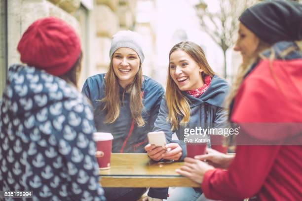 Las mujeres jóvenes divierten en un café