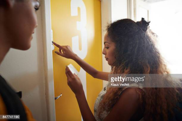 Young women arriving to room and pushing door code, at youth hostel