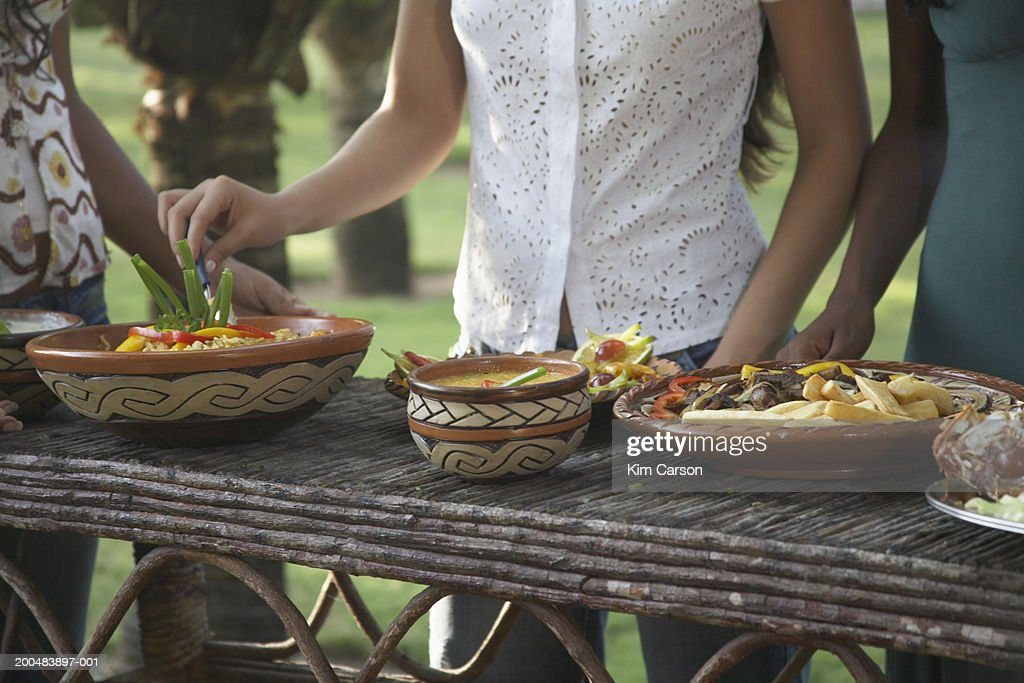 Young women at outdoor buffet, mid section : Stock Photo