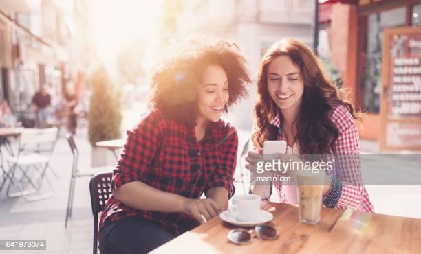 Jonge vrouwen op sidewalk café
