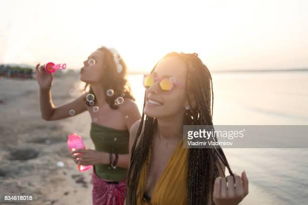 Jeunes femmes soufflant des bulles sur la plage