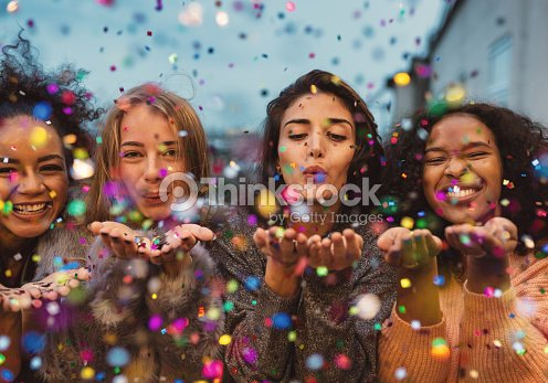 Young women blowing confetti from hands. : Stock Photo
