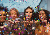 Young women blowing confetti from hands. Friends celebrating outdoors in evening at a terrace.