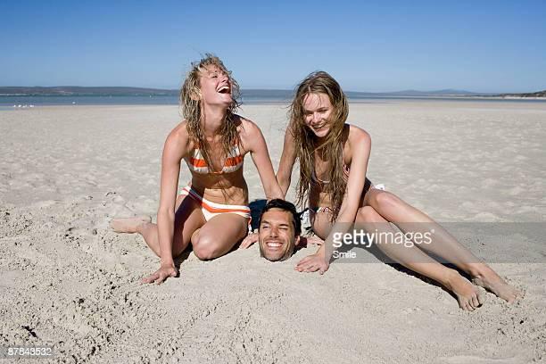 young women burying man in sand laughing