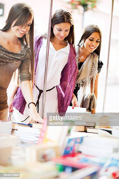 Young women buying books.