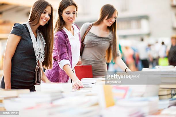 Young women buying books.