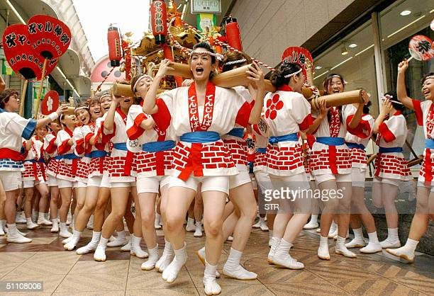 Young women carry a portable shrine weighing 200kg on their shoulders at the Tenjin Matsuri festival in Osaka western Japan 23 July 2004 Some 80...