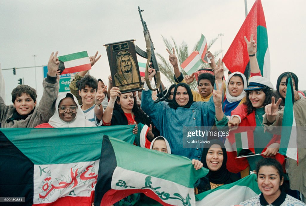Young women celebrate after the Iraqi troops were driven from Kuwait during the Gulf War 1991 One holds a portrait of Sheikh Jaber AlAhmad AlSabah...