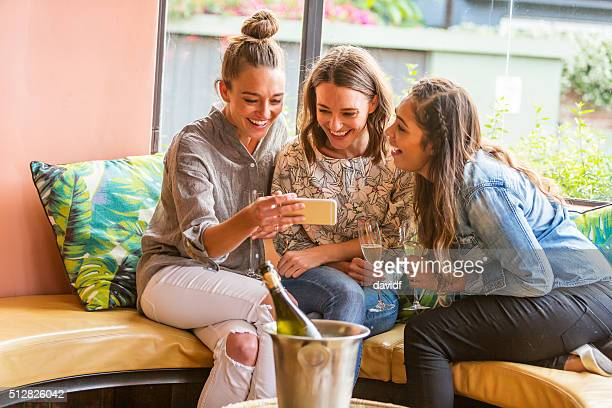 Young Women Celebrating and Laughing With A Phone and Champagne