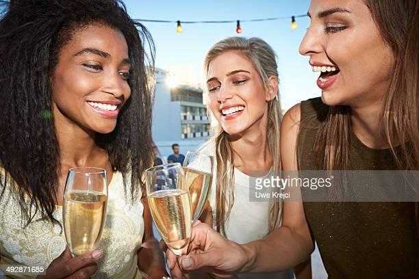 Young women celebrating, raising champagne flutes