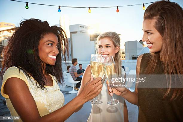 Young women celebrating, raising champagne flutes