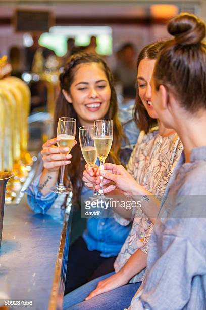 Young Women Celebrating With Champage in a Bar