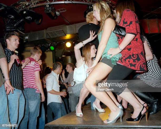 Young women dance on a raised platform at the Walkabout bar in Blackpool April 2007