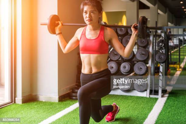 Young women doing barbell squats at gym