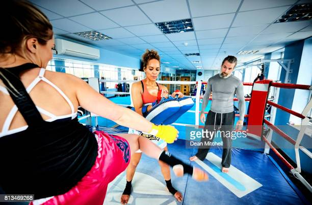 Young women doing kickboxing training with their coach