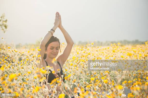 Young Women Doing Yoga In A Flower Field
