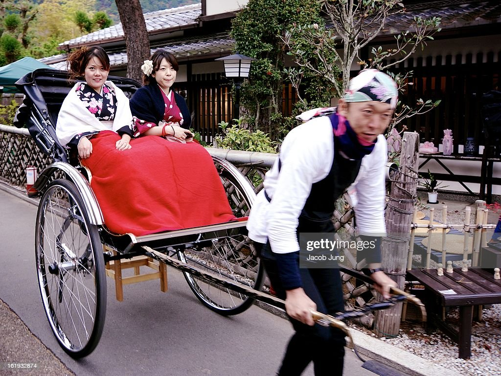 CONTENT] Young women dressed in kimono with a blanket over their laps are pulled along in a rickshaw in Kyoto's scenic Arashiyama district during the height of the autumn foliage season. Nishikyo Ward, Kyoto, Japan. November 28, 2012.
