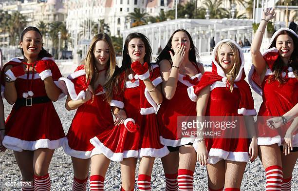 Young women dressed in Santa Claus outfit blow kisses as they pose within the traditional Christmas bath on December 21 2014 on the beach in downtown...