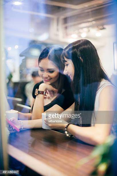 Young women drink coffee, using smart phone, coffee shop, Tokyo