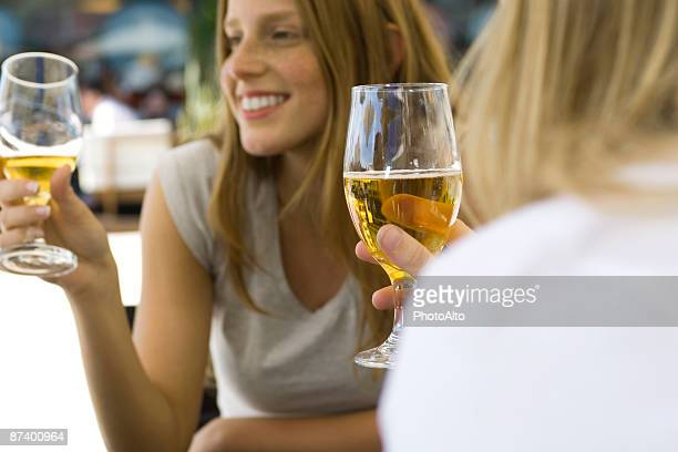 Young women drinking beer at sidewalk cafe, cropped