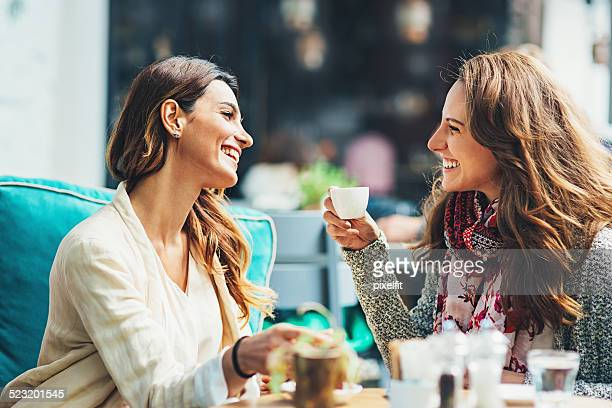 Young women drinking coffee and smiling