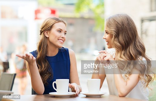 young women drinking coffee and talking at cafe : Stock Photo
