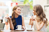 people, communication and friendship concept - smiling young women drinking coffee or tea and talking at outdoor cafe