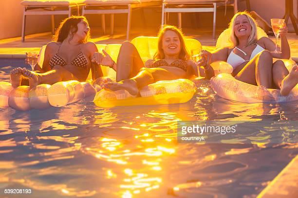 Giovane donna bere su lilos alla festa in piscina.