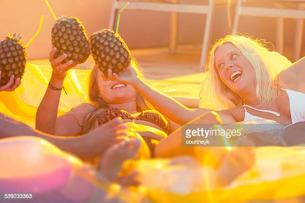 Young women drinking on lilos at pool party.
