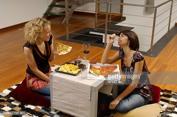Young women eating at dinner table, elevated view