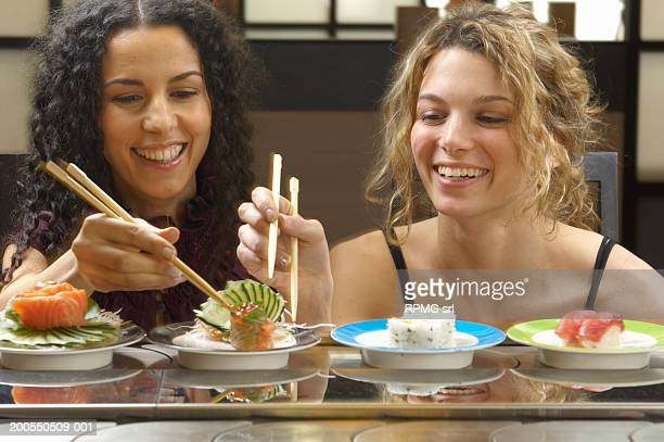 Young women eating sushi wioth chopsticks, smiling