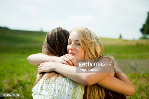 Young women embracing in a field : ストックフォト