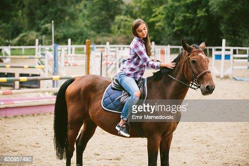 Young women enjoying horseback riding and stroking a horse