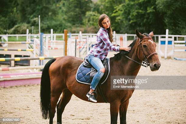 Young women enjoying horseback riding and stroking a horse